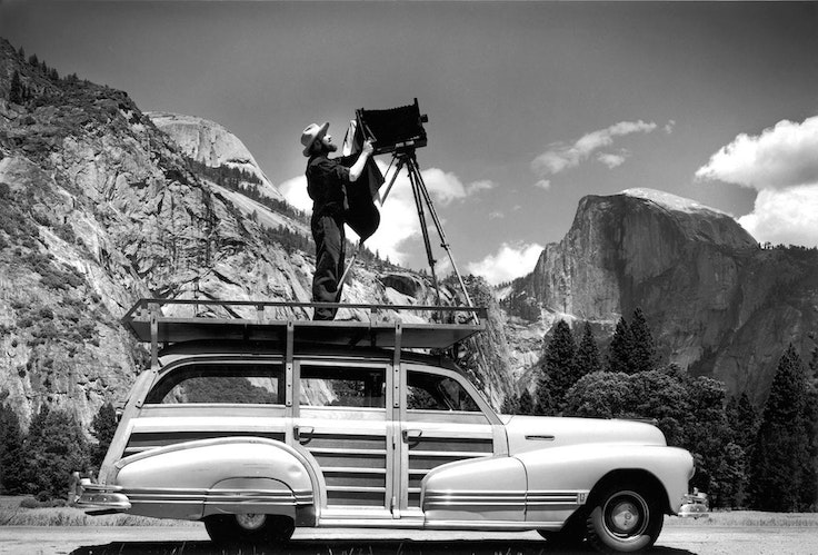 Ansel Adams, photographing in Yosemite National Park from atop his car in about 1942.