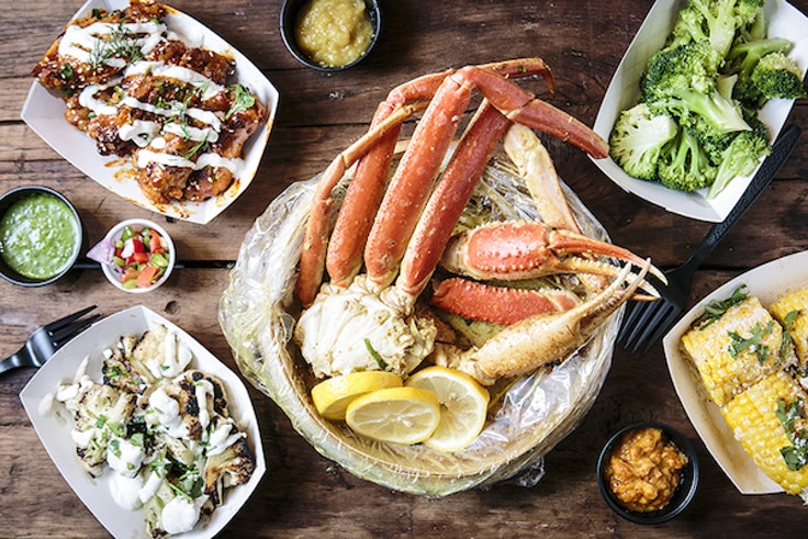 Fresh snow crab legs surrounded by sides, served at LoLo's Seafood Shack