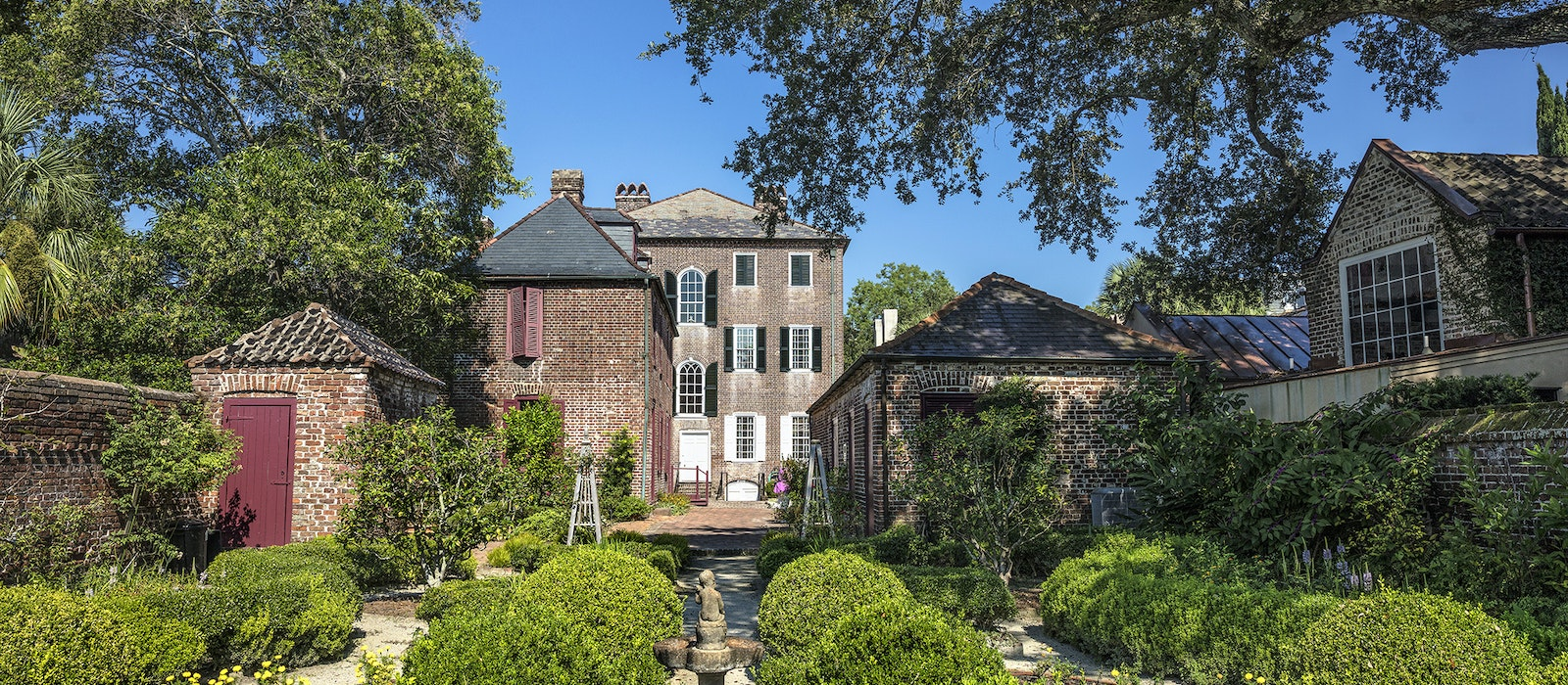 The forbidding walls in Charleston's South of Broad neighborhood hide private gardens, pools, fountains, and historic outbuildings.