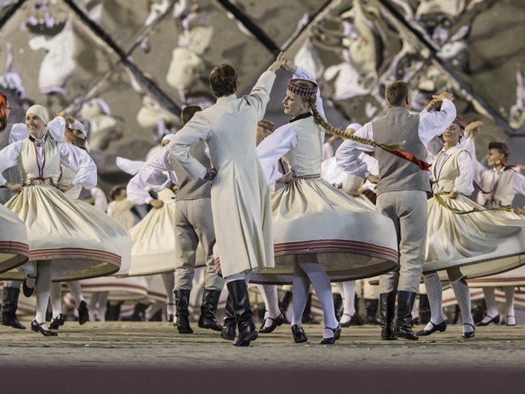 Dancers in traditional costumes perform at the Latvian National Song and Dance Festival.