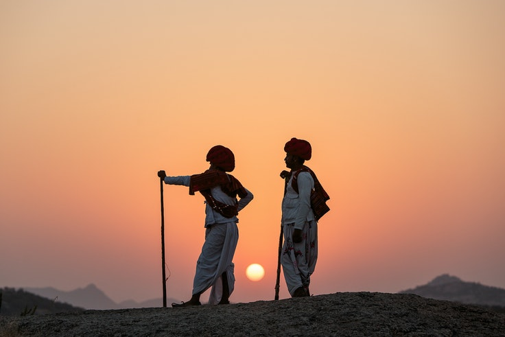 Two Rabari tribesmen watch the sunset in a rural village near the ancient hills of Jawai in Rajasthan, India.