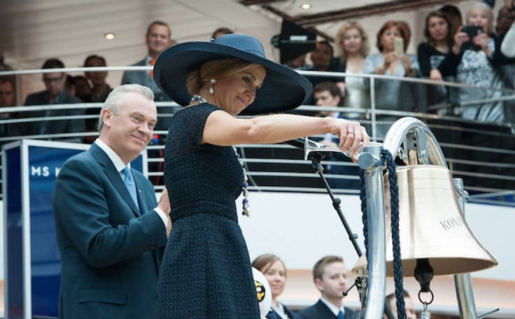 Queen Máxima of the Netherlands douses the bell of the Koningsdamwith champagne.