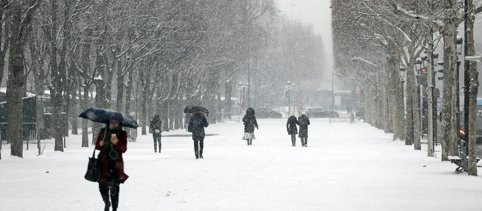 People stroll on the Champs-Elysées as it snows in Paris on January 22, 2019.