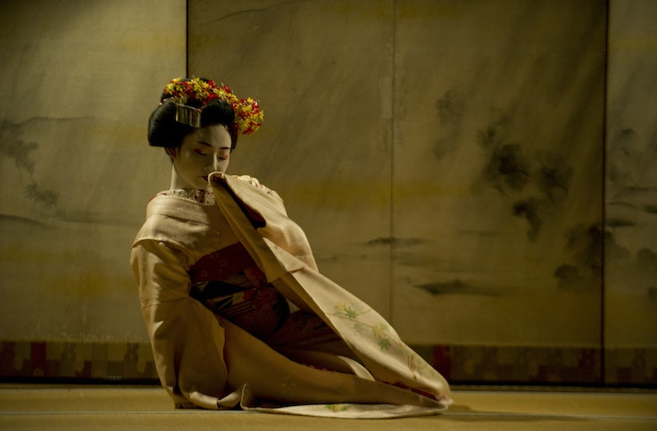 A maiko (an apprentice geisha) performs a traditional dance at a temple in Kyoto, Japan.