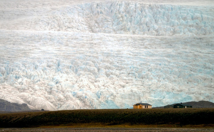 A house perched at the edge of a glacier