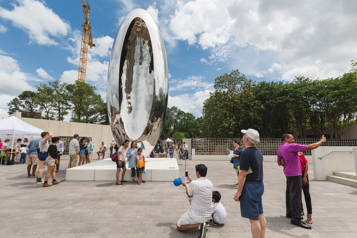 """Visitors to the Brown Foundation Plaza near the Glassell School of Art check out """"Cloud Column"""" by Anish Kapoor."""