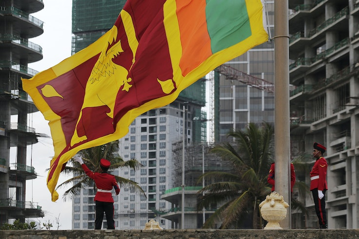 Members of the Sri Lankan army lower the national flag at the landmark Galle Face in Colombo, Sri Lanka.
