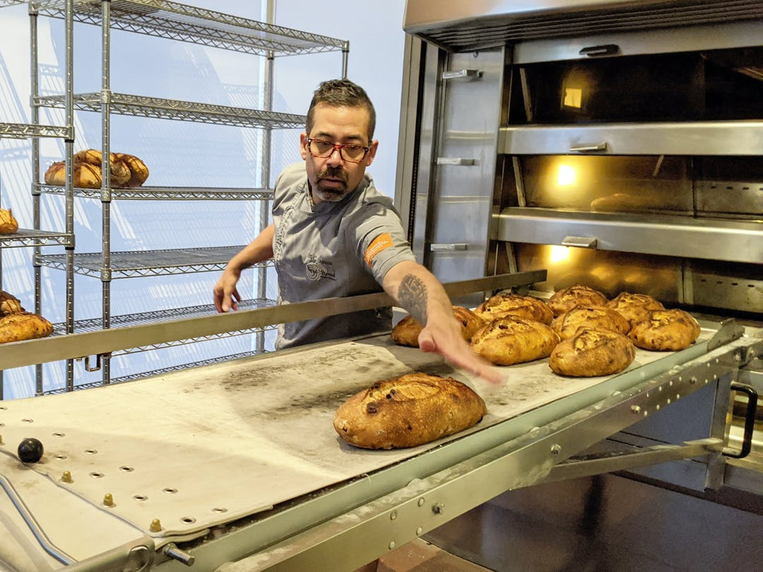 Don Guerra clears cranberry walnut loaves off the oven conveyor belt at his bakery, Barrio Bread, in Tucson, Arizona.