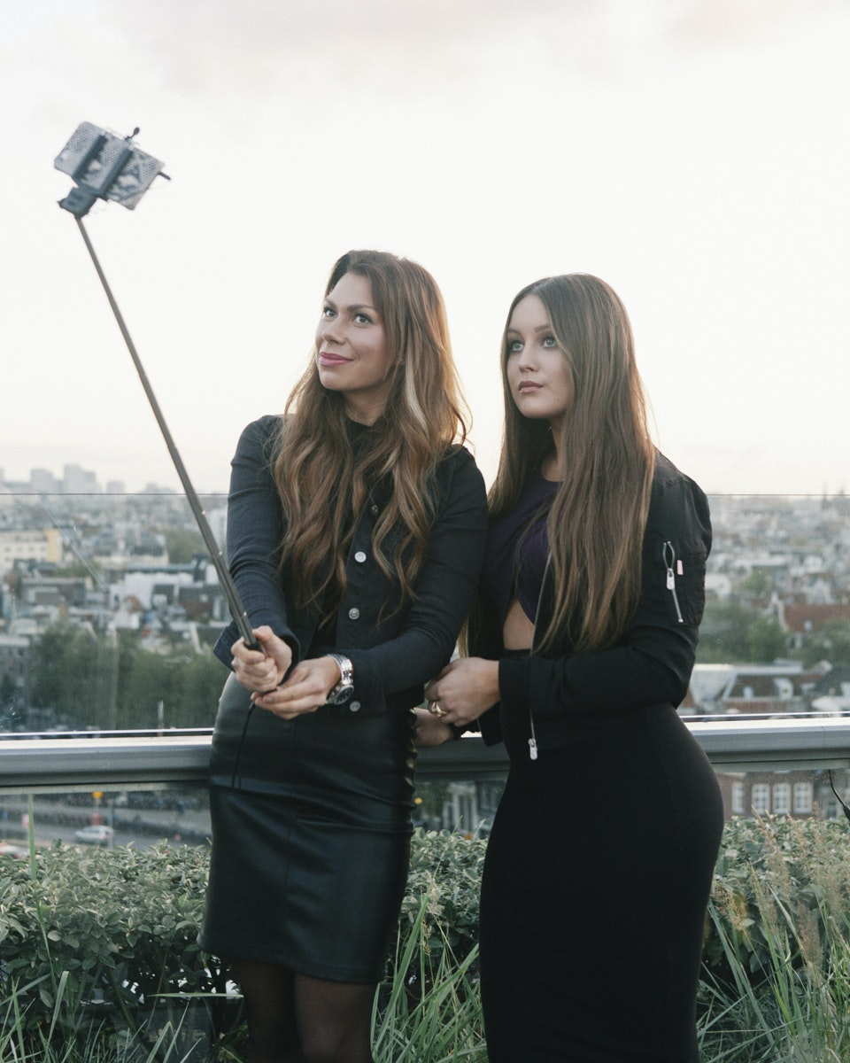 Two women pose for a selfie with the city of Amsterdam as their backdrop.