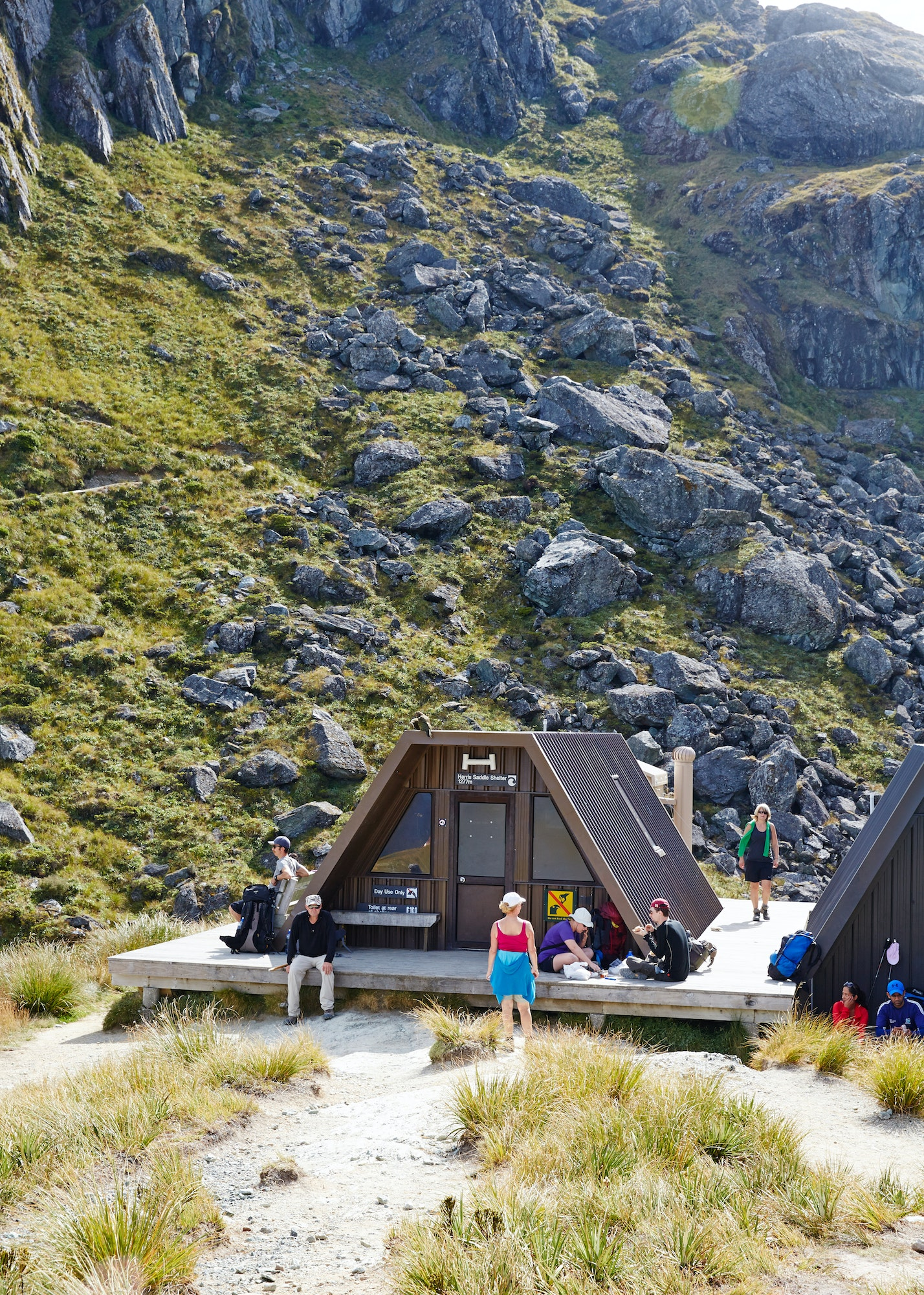 After a long day of trekking, hikers enjoy a rest at the trailside Harris Saddle warming huts.