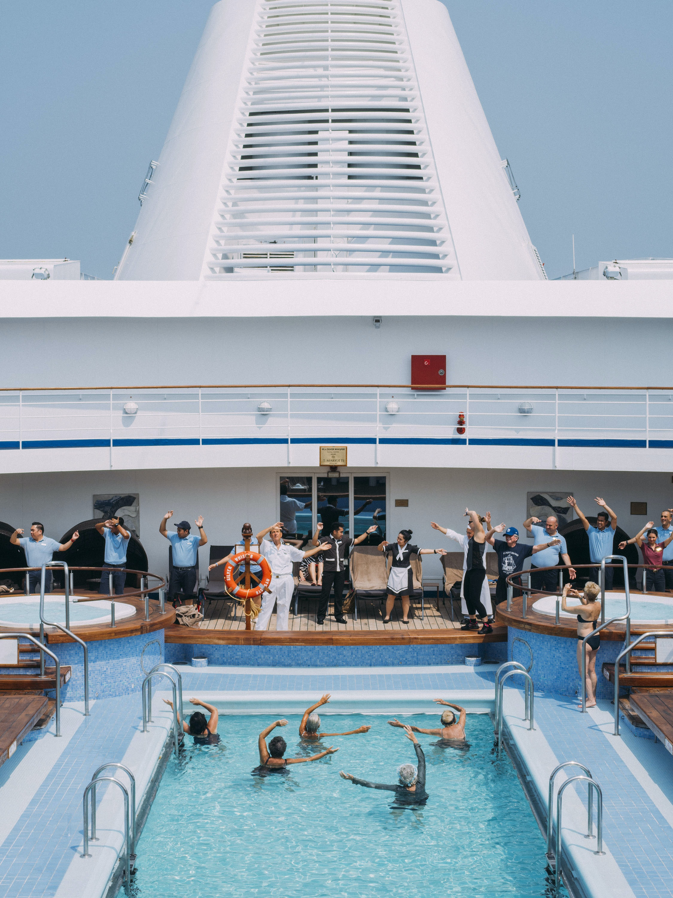 Many of the ship's crew members join in for the choreographed opening warm-up to the daily water aerobics class in the upper-deck outdoor pool of the Silver Whisper.