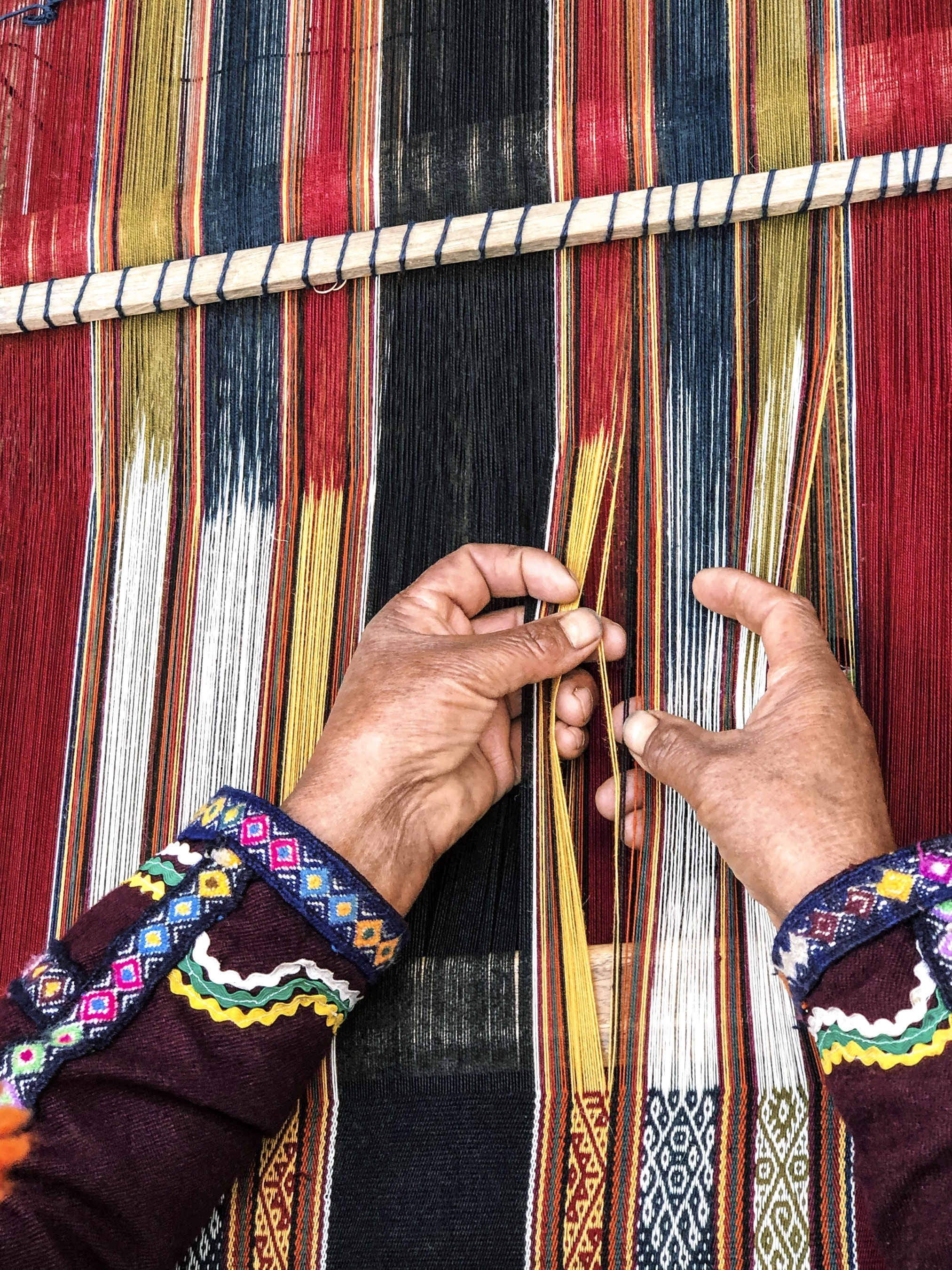 A weaver from the indigenous Amaru community works on a table runner.