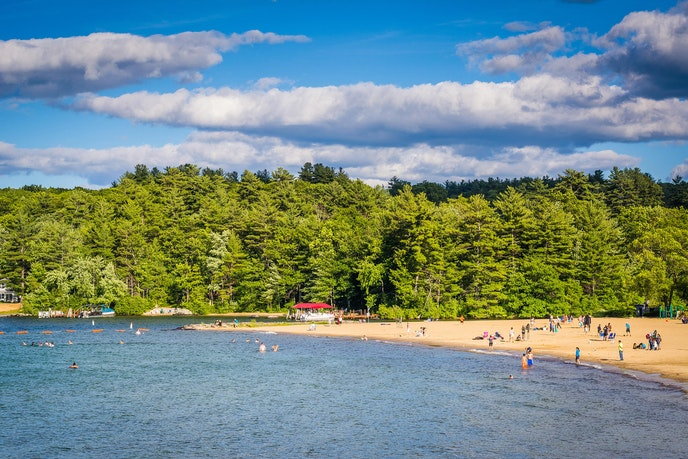 Forests meet the beach at Weirs Beach on Lake Winnipesaukee in New Hampshire.