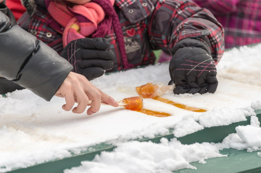 Diners enjoying maple taffy on a bed of fresh snow.