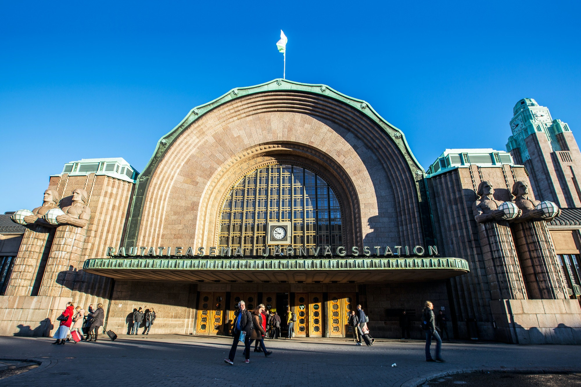 Lantern-carrying giants stand guard on either side of the entrance to Helsinki Central Station.