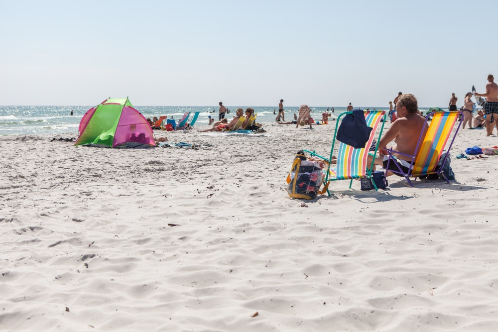 Vacationers enjoy the white sand beaches of Bornholm.