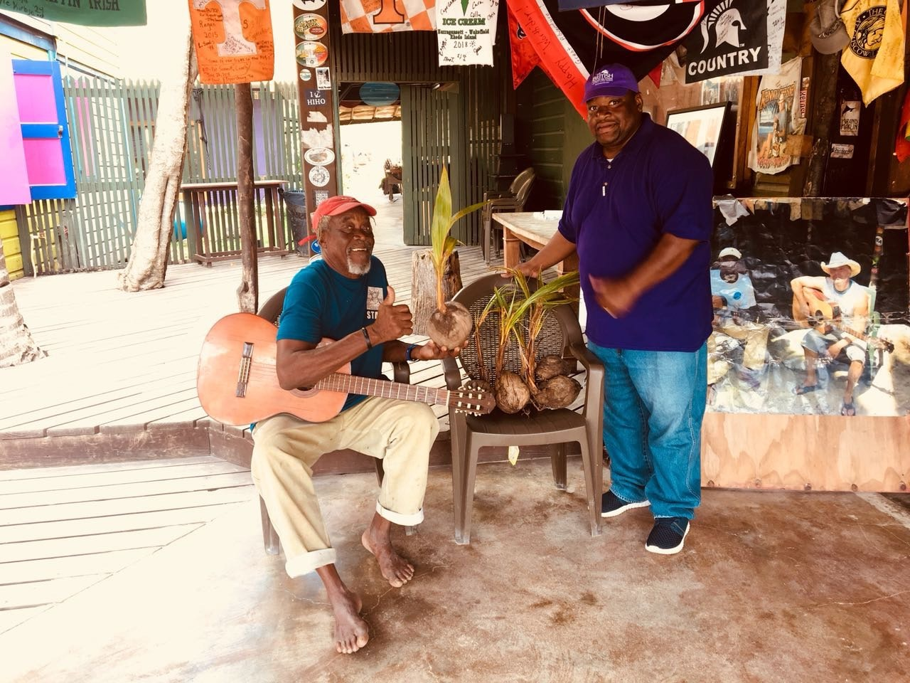 "On Jost Van Dyke, product officer Arvan Hodge presents seedlings to the BVI's one and only Philicianno ""Foxy"" Callwood, left."