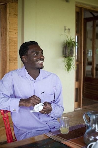 Patrick Otim unwinds on his cottage balcony at Bwindi Lodge.
