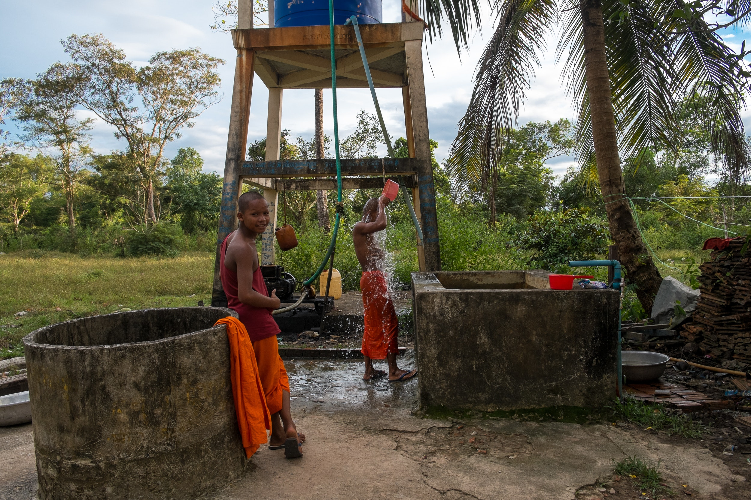 Local monks shower just outside of Chi Phat