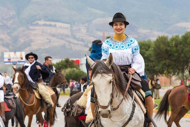 Ecuadorian cowboys paraded in traditional clothing: sheepskin chaps for men and embroidered blouses and fedoras for women.