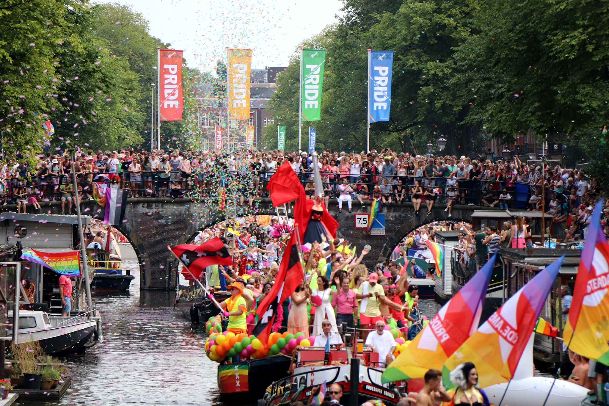 Boats float down Amsterdam's canals as part of the Amsterdam Canal Parade in 2018.