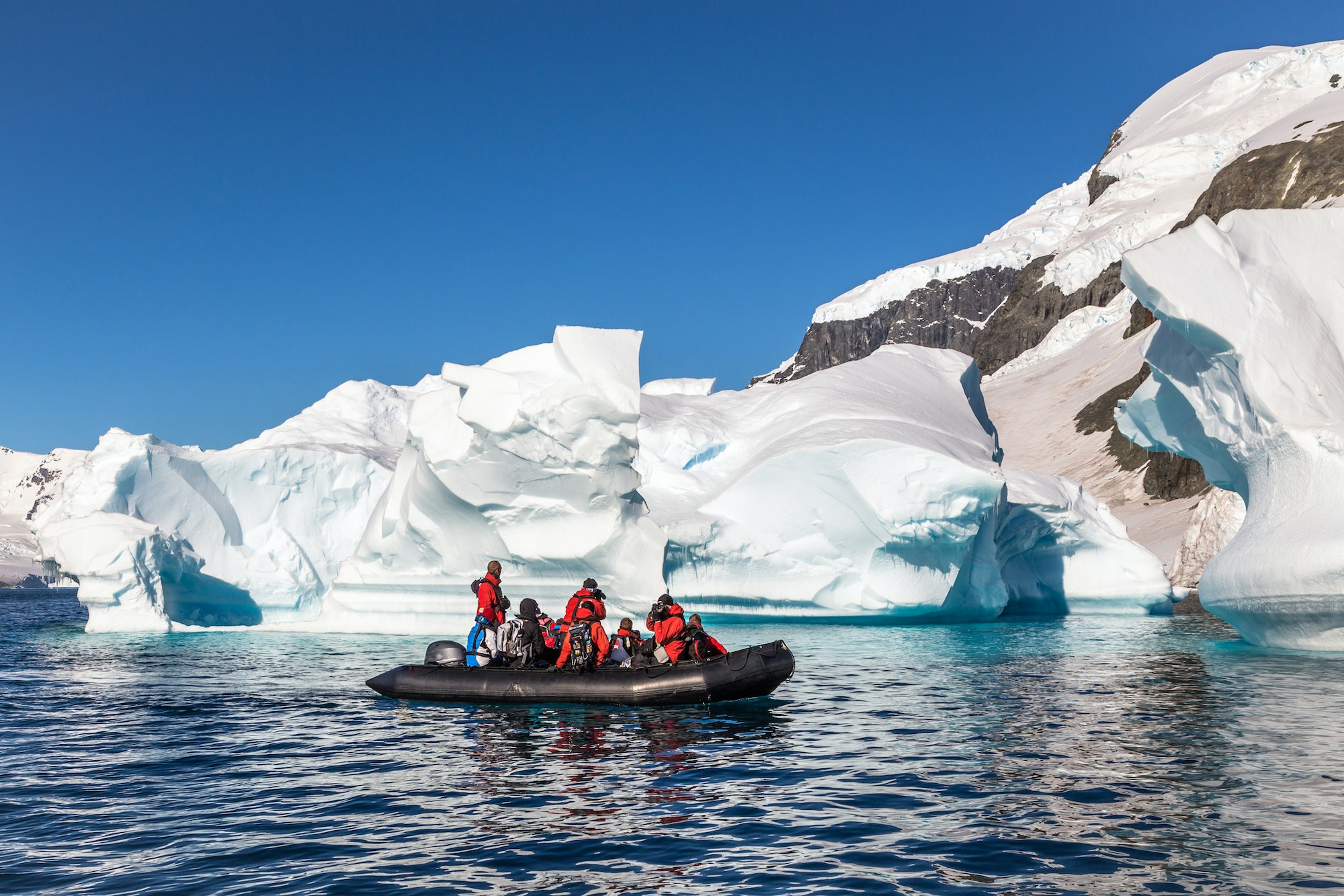 Small groups in Zodiac boats pass icebergs in the Antarctic Peninsula.