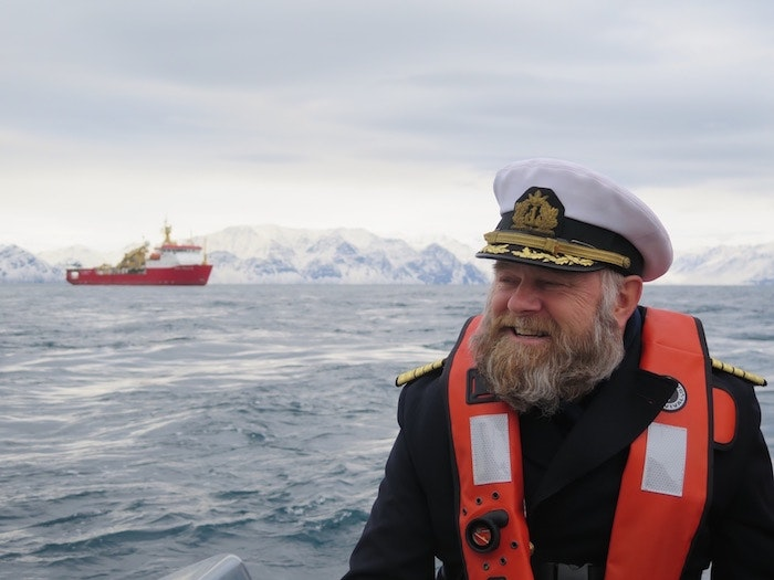 Captain Birger Vorland rides a zodiac to Pond Inlet; Crystal Serenity's icebreak escort appears behind him.
