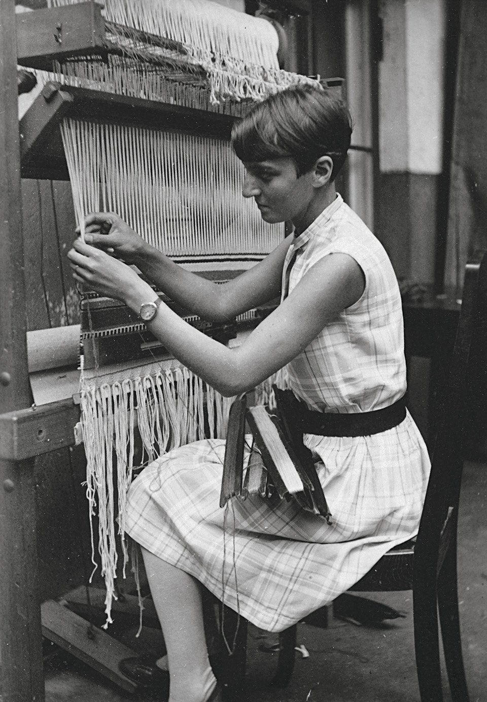 Ruth Consemüller, a textile design artist at the Bauhaus, works at the loom in a dress made of fabric woven by herself, c. 1931