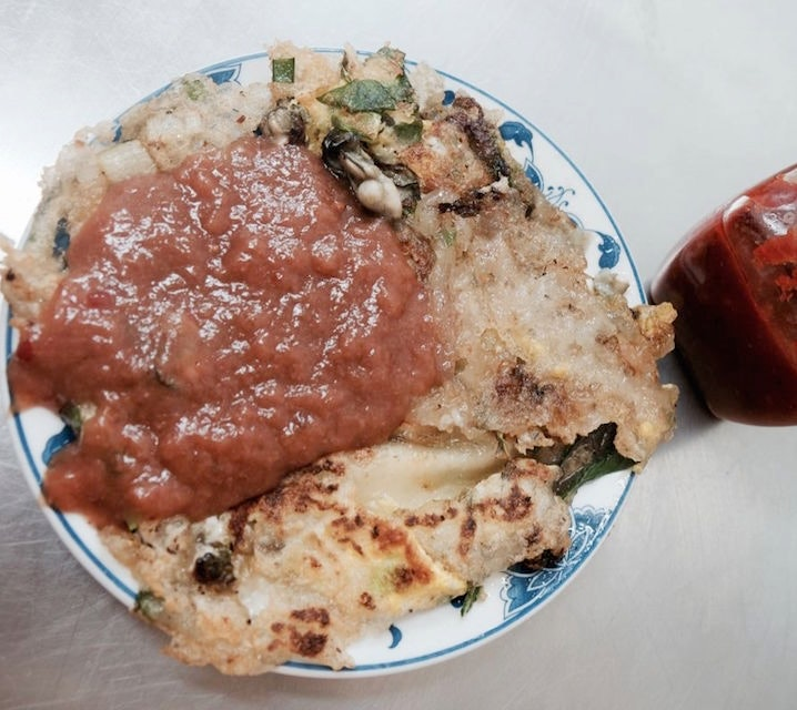 An oyster omelet topped with chili sauce.