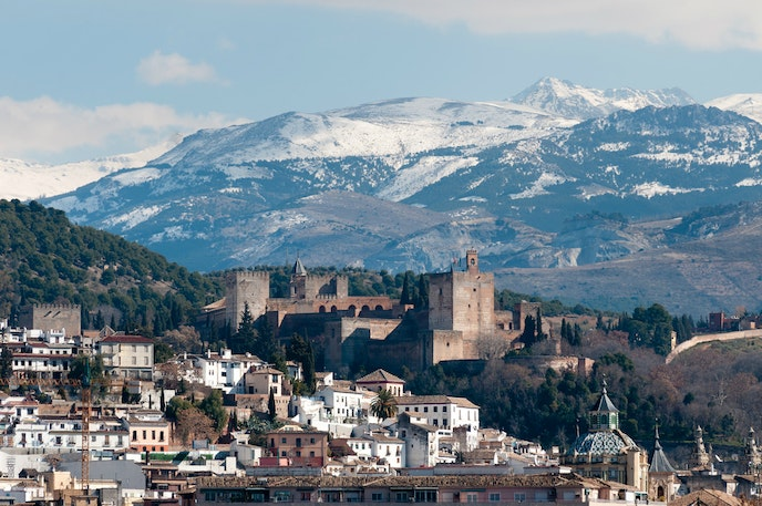 A winter scene of Spain's famous Alhambra, with the snowcapped Sierra Nevada in the background.