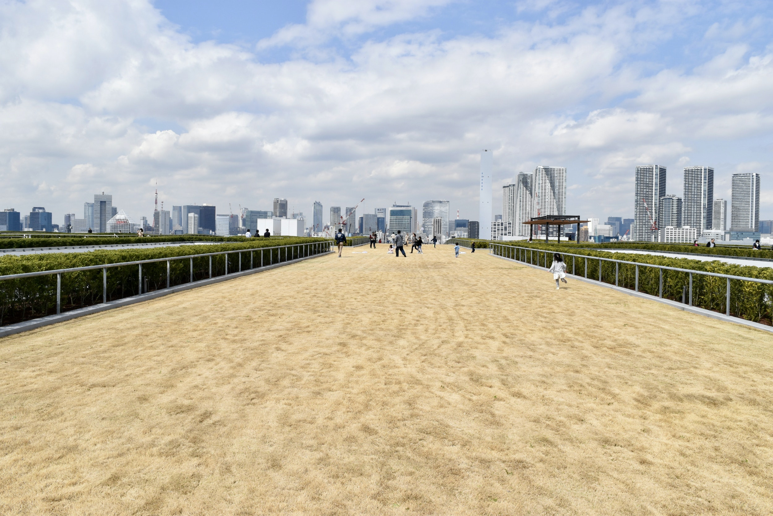 A spacious rooftop garden area at Toyosu Market features landscaping and nice views out onto Tokyo Bay and the city.