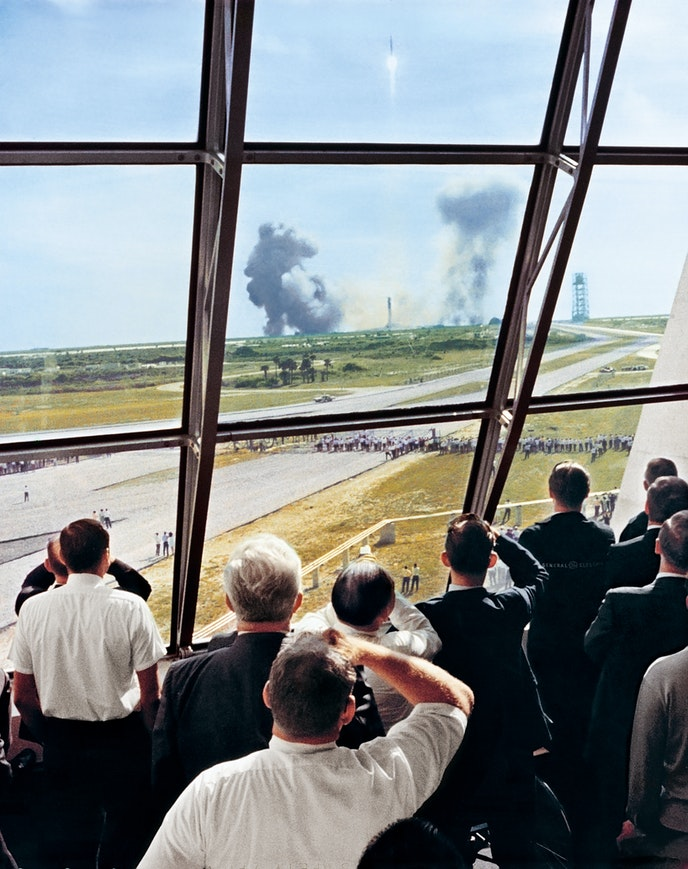 """Crowds gather at NASA's Launch Control Center as the Saturn V rocket launches """"Apollo 11""""'s mission to the moon."""