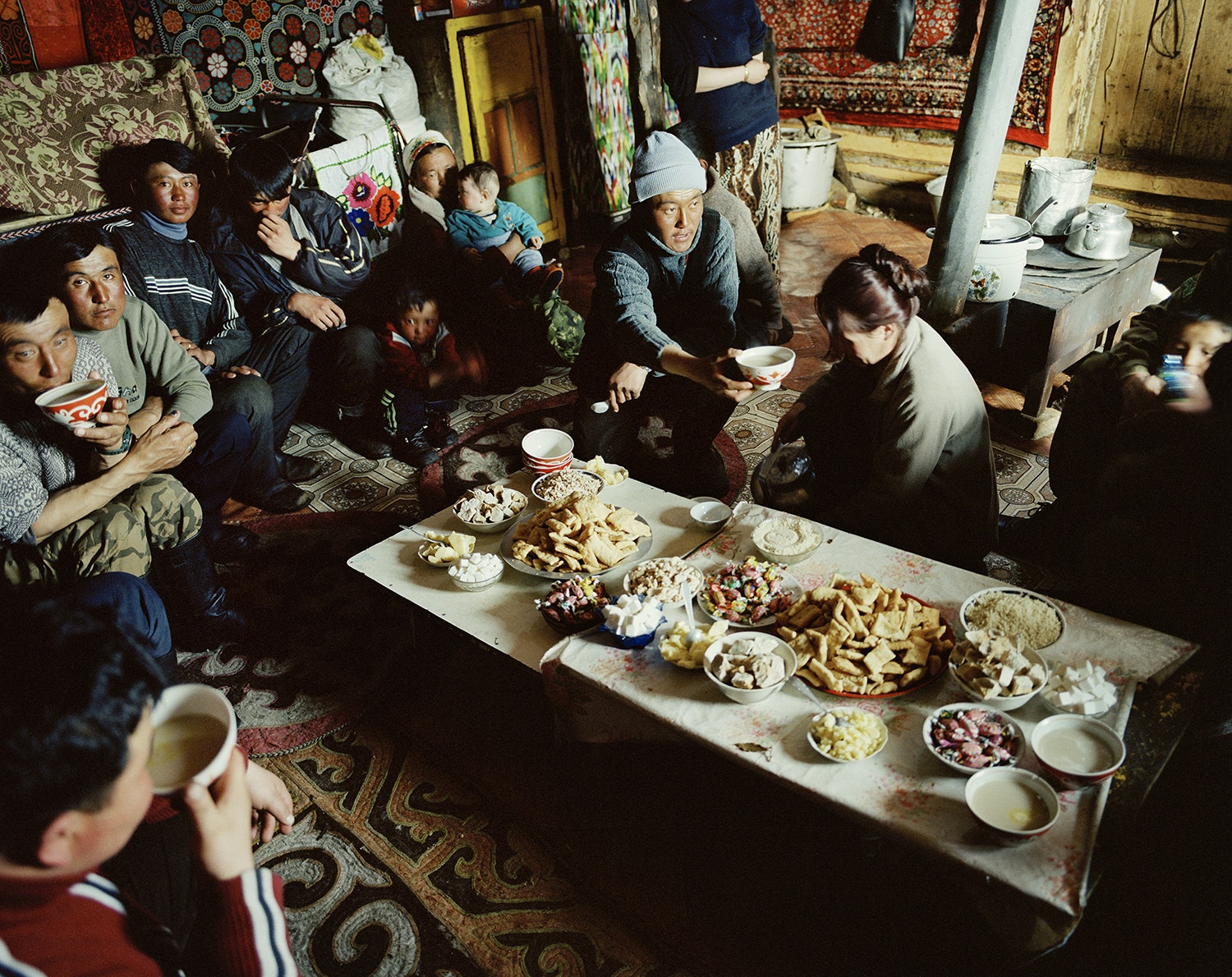 A nomadic family in Mongolia's Tsengel village gathers in their ger (portable tent) for a meal. The people in this area, near the Kazakhstan border, are known for practicing the ancient sport of eagle hunting.