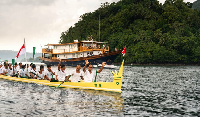 Traditional kora kora boats lead the Rascal out from the Banda Islands.