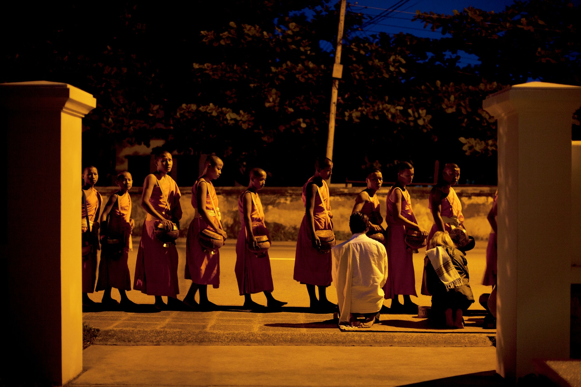 Some monks participating in the predawn tak bat ritual pass right in front of Amantaka.