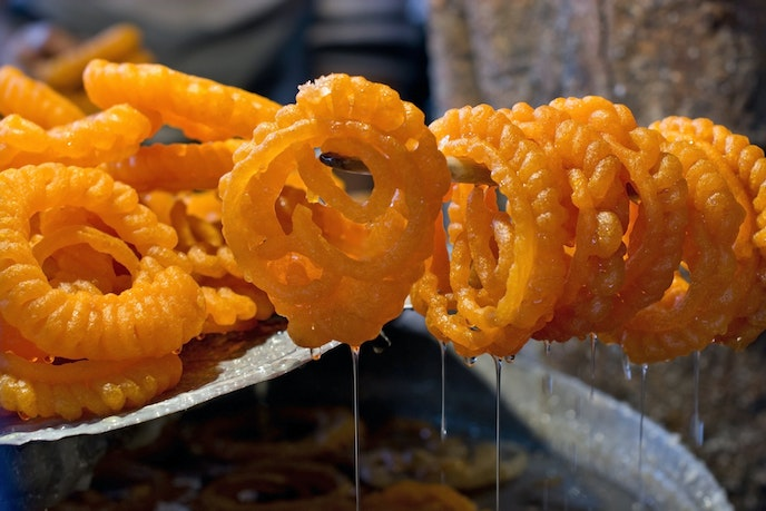 Jalebi, spirals of fried dough drenched in sugar syrup, hang from a stick to let the excess syrup drip off.