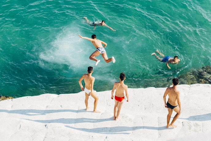 Young Italian men find their dolce far niente by jumping from the Scala dei Turchi cliff on the Realmonte coast in southern Sicily.