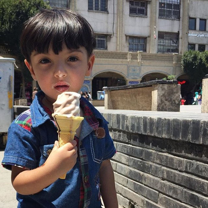 A little Iranian boy enjoys his ice cream.