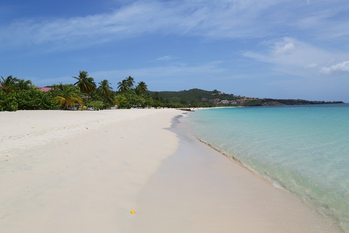 At Grenada's Grand Anse Beach, nearly two miles of dazzling white sand are lapped by calm, warm Caribbean seas.