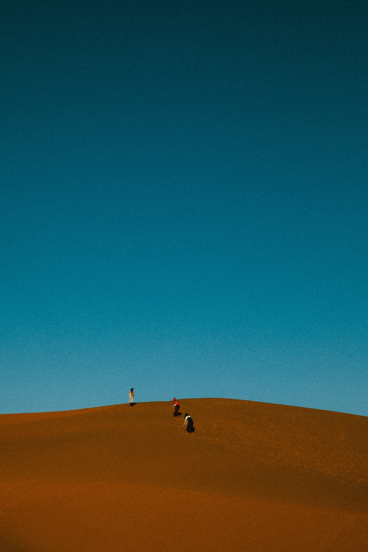 Travelers climbing the last steps to get to the high dunes to watch a full 360 view of the sunset over the dunes.