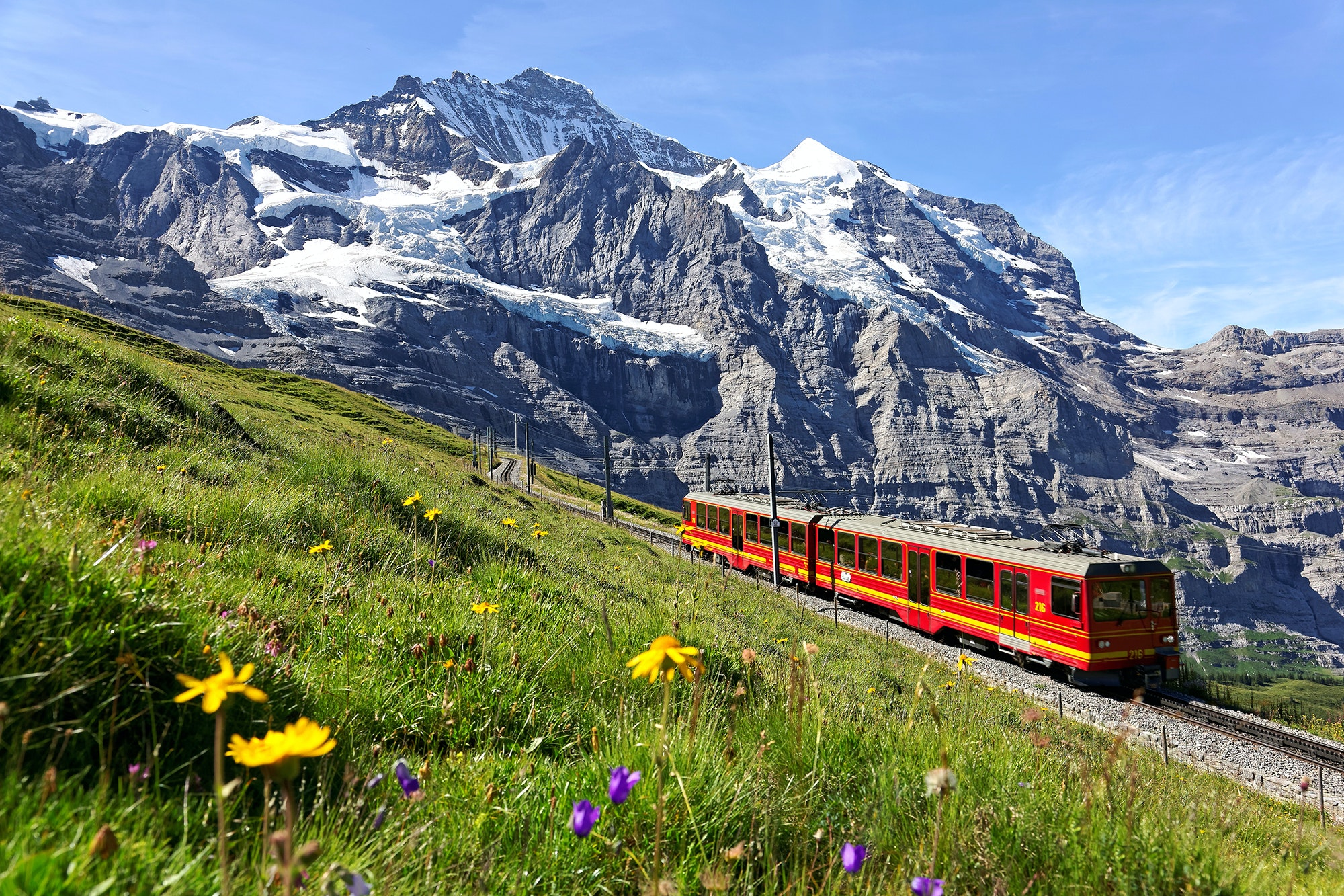 The Jungfrau Railway passes by grassy hillsides in the Bernese Oberland before reaching the highest-altitude train station in Europe.
