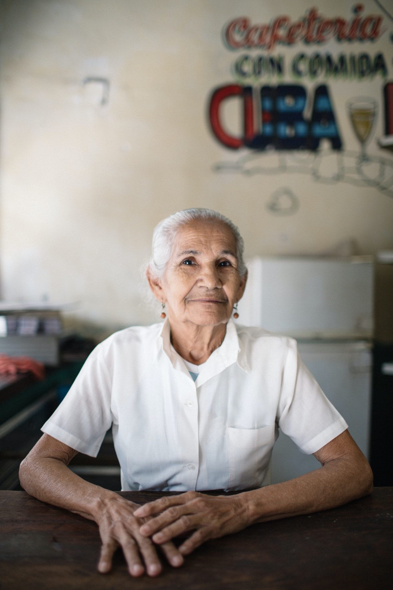 A woman gives a slight smile for Laucht's camera in a local restaurant in Cuba.