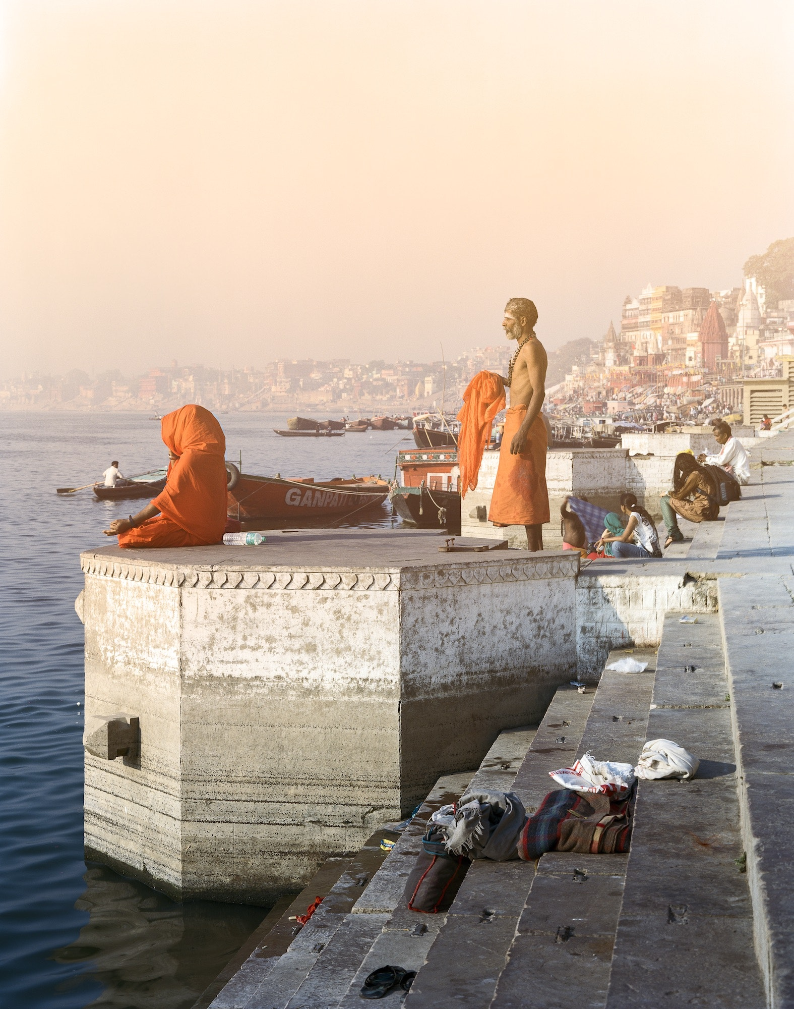A standing sadhu and a sitting meditator embody the stillness of morning prayer on the ghats along the Ganges River.