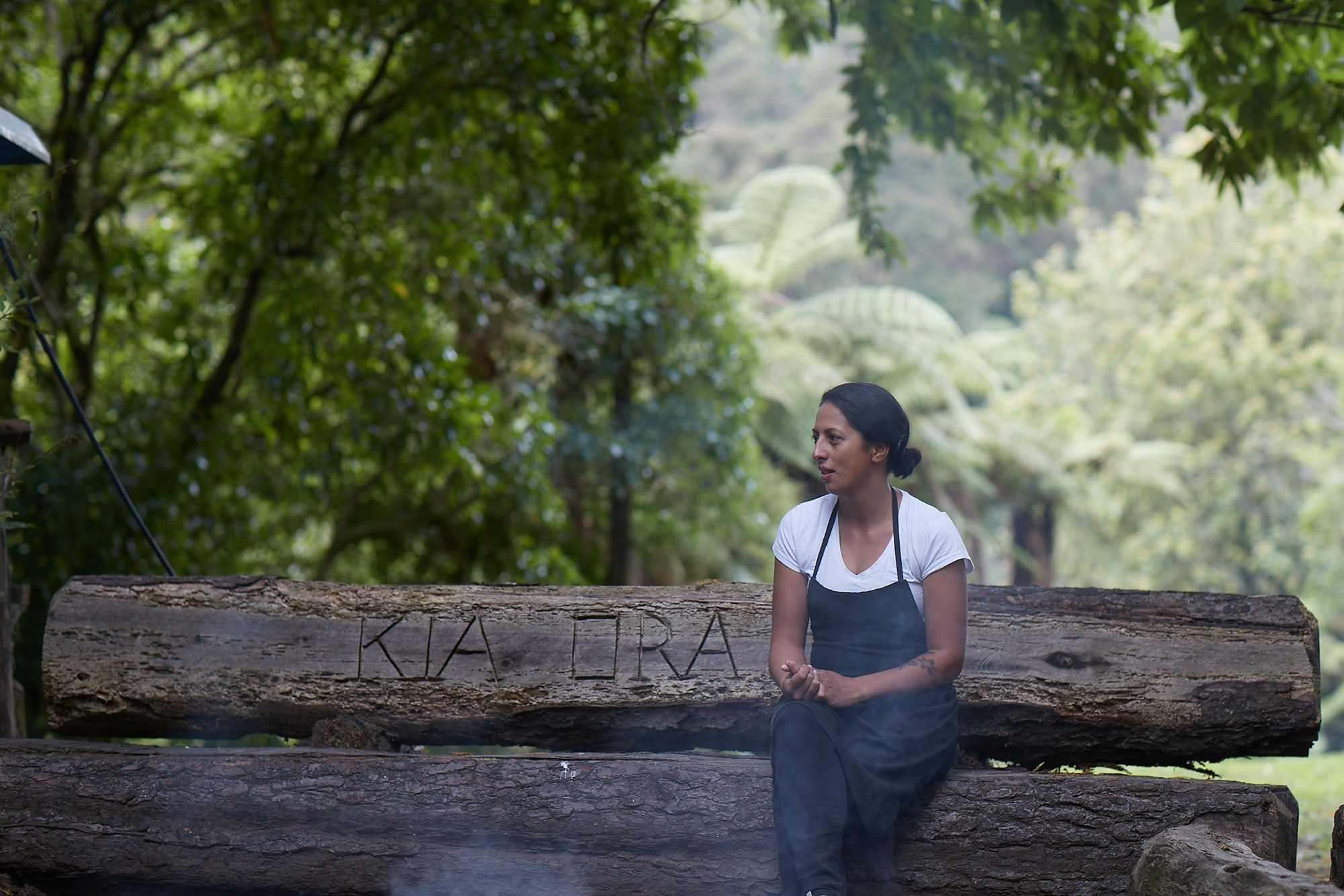 """Fiso, on a bench carved with the Māori greeting """"kia ora,"""" is glad Māori food is getting the recognition it deserves."""