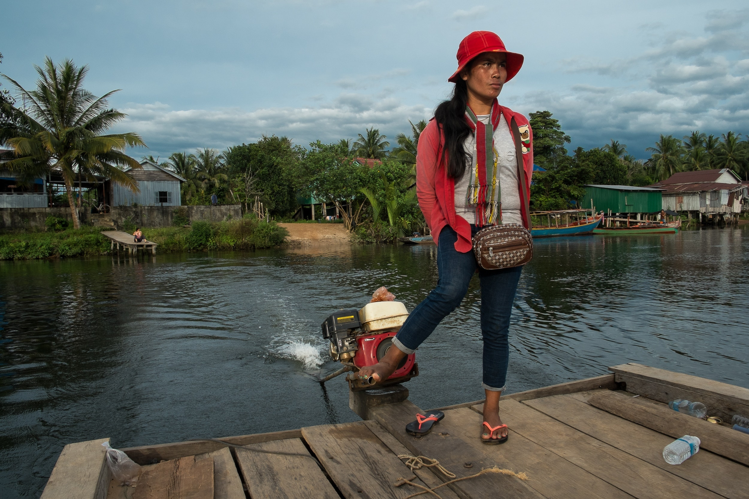 A woman steers a ferry across the river in Chi Phat
