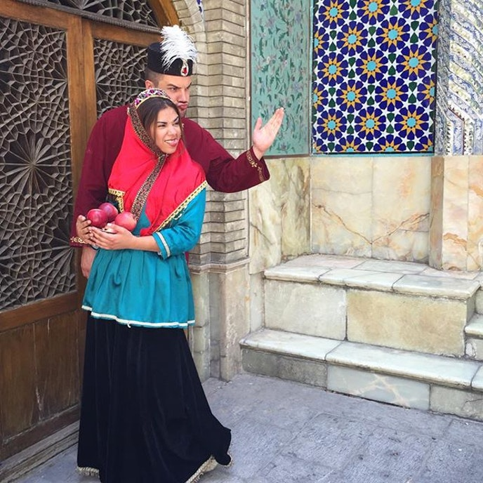 A young couple, dressed in traditional Qajar Era costume, make funny poses for a photograph at Golestan Palace, Tehran.