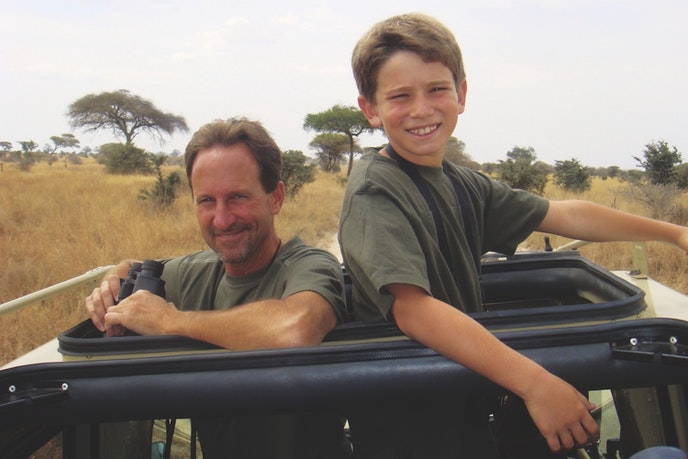 A father and son on a game drive with Tauck