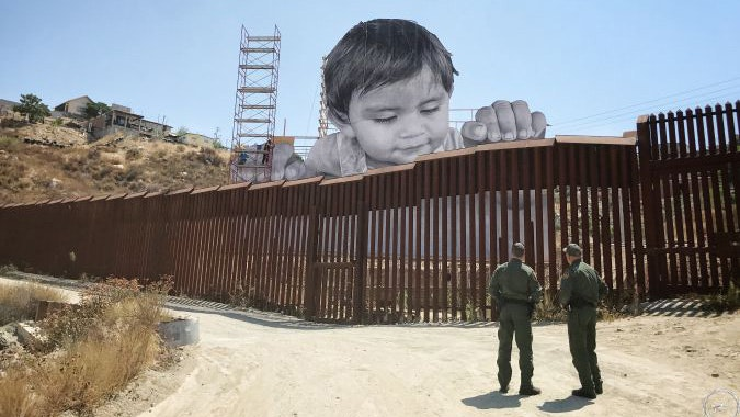 A massive photo of baby Kikito peers over the border fence in Tecate.