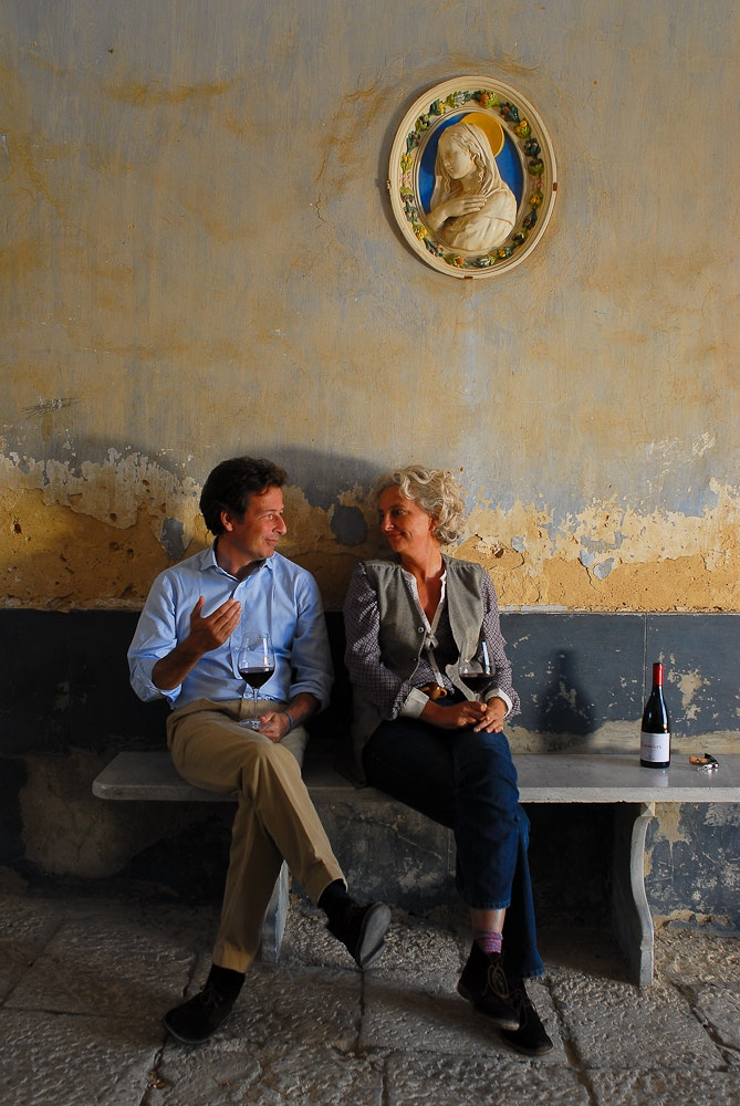 Alberto Tasca, the son of Count Lucio Tasca, shares a bottle of Rosso di Conte with his cousin, Fabrizia Lanza, who runs a nearby cooking school.