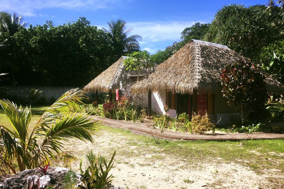 The thatch-roof bungalows at Vaitumu Village are set in a garden and enjoy ocean views.